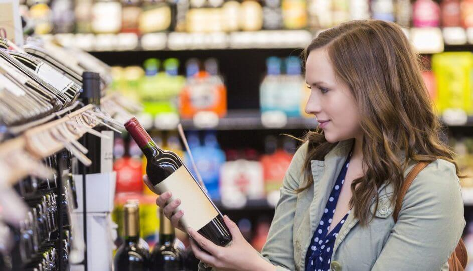 Pretty woman picking out wine at store