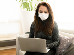woman working from home on laptop with a mask